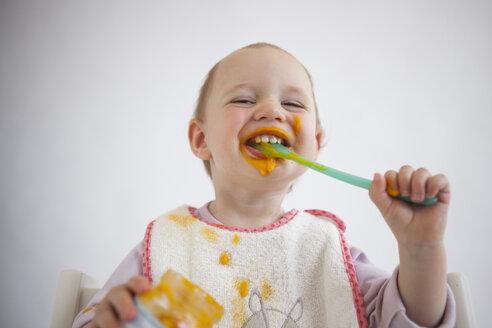 Portrait of funny baby girl eating mush - JLOF00290