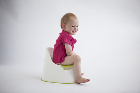 Laughing baby girl sitting on potty - JLOF00293