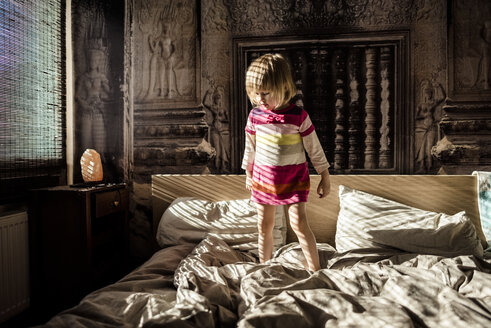 Little girl standing on parent's bed at home - PSIF00127