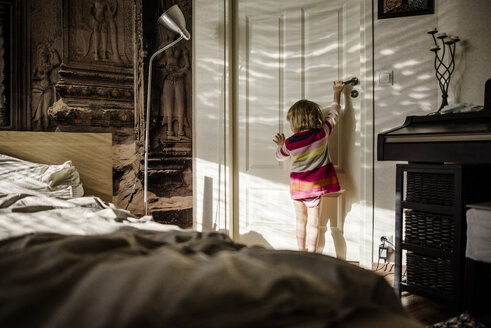 Back view of little girl opening bedroom door at home - PSIF00130