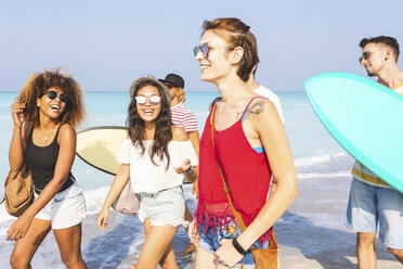 Group of friends walking on the beach, carrying surfboards - WPEF00953