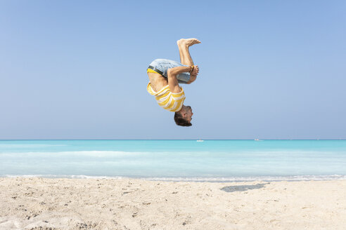 Young man doing a somersault on the beach - WPEF00980
