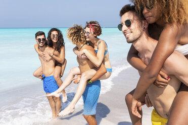 Friends walking on the beach, carrying girlfriends piggyback - WPEF01028