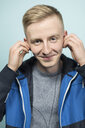 Portrait of smiling young man putting on earphones - VGF00075