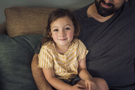 High angle portrait of girl sitting with father on sofa at home - CAVF51420