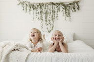 Cheerful siblings lying on bed at home - CAVF51447