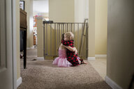 Side view of siblings embracing on carpet at home - CAVF51450