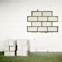 White blocks piled up in front of a white wall with green lines - INGF03518