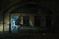 Creative shot of a man hiding on a doorway at night - INGF03698