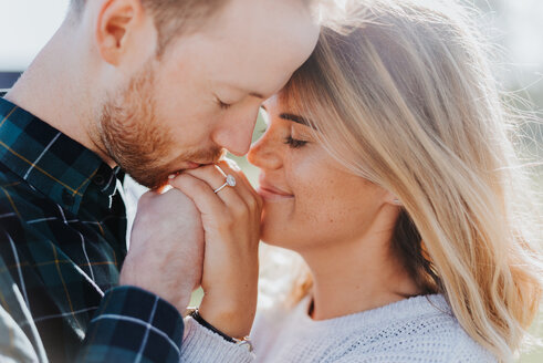 Newly engaged couple kissing - CUF46331