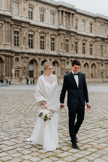Bride and bridegroom on cobblestone street, Paris, France - CUF46337