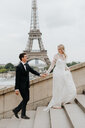 Bride and bridegroom, Eiffel Tower in background, Paris, France - CUF46340