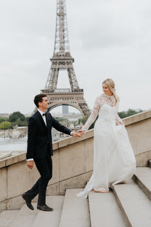 Bride and bridegroom, Eiffel Tower in background, Paris, France - CUF46340