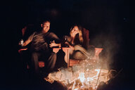 Couple sitting by camp fire, Algonquin Park, Canada - CUF46349