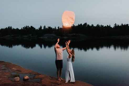 Couple releasing sky lanterns by lake, Algonquin Park, Canada - CUF46367