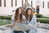 Girlfriends reading street map at piazza, Belluno, Veneto, Italy - CUF46463