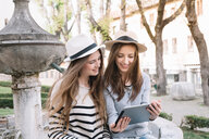 Girlfriends using digital tablet at piazza, Belluno, Veneto, Italy - CUF46466
