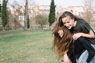 Girlfriends playing piggyback ride in park - CUF46469