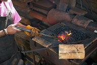 Blacksmith working in his forge - CUF46502