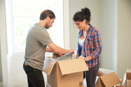 Couple packing mirror into cardboard box - CUF46523