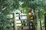 Hiker couple opening farm gate - CUF46529