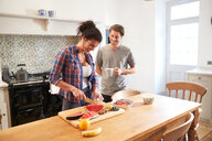 Couple slicing fresh fruit and chatting at kitchen table - CUF46541