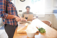 Woman preparing vegetables at kitchen table, boyfriend using laptop - CUF46544