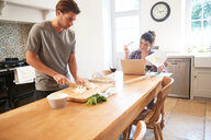 Man preparing vegetables at kitchen table, girlfriend using laptop - CUF46547
