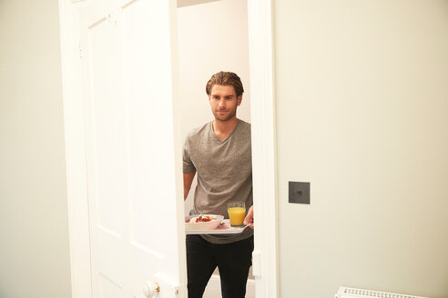 Young man carrying breakfast tray into bedroom - CUF46550