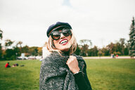 Blond woman wearing sunglasses in park, portrait - CUF46553