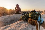 Rock climber on summit at sunset, Joshua Tree, California, USA - ISF20027