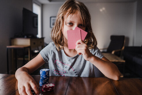 Girl hiding behind playing cards with gambling chips at table, portrait - ISF20039