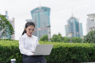 Young businesswoman typing on laptop in city financial district, Shanghai, China - ISF20066