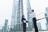 Young businesswoman and man talking in city financial district, Shanghai, China - ISF20069