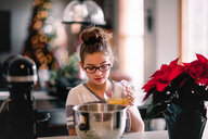 Girl pouring egg yolk into mixing bowl for christmas cookies at kitchen counter - ISF20090