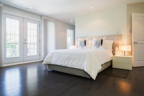 Master bedroom with queen size bed and dark wooden flooring, upstairs inside luxury residential home - ISF20114