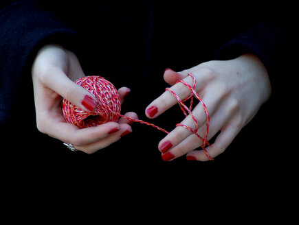 Hands and fingers entwined with red ball of string - INGF03913
