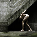 Naked man under urban stone steps - INGF03961