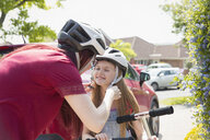Mother fastening helmet on daughter riding scooter in sunny driveway - CAIF22193