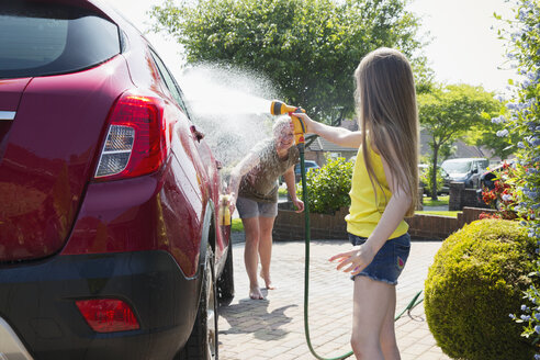 Mother and daughter washing car in sunny driveway - CAIF22196