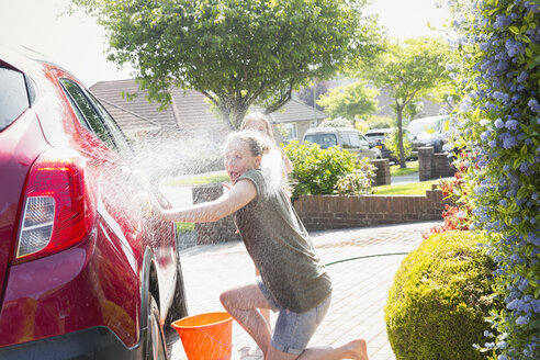 Playful daughter spraying mother with hose, washing car in sunny driveway - CAIF22199