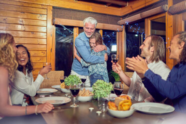 Friends clapping for affectionate couple hugging at dinner table - CAIF22250