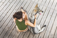 Young woman sitting besides her dog on plank floor, top view - WPEF01075