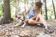 Smiling young woman sitting on forest floor stroking her dog - WPEF01078