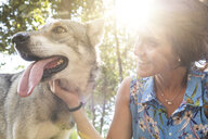 Smiling young woman stroking her dog at backlight - WPEF01081