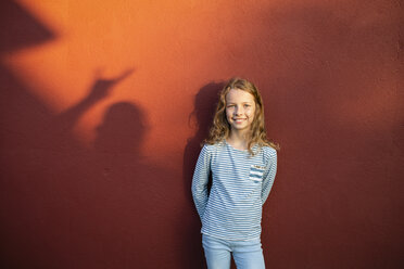 Portrait of smiling girl in front of a red wall with shadow - OJF00266