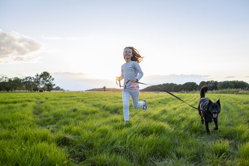 Girl with a dog running over a field at sunset - OJF00272