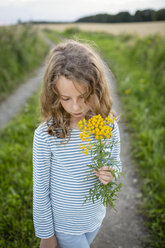 Girl standing on field path holding a wild flower - OJF00275