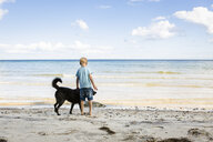 Boy stroking dog at the beach - OJF00281