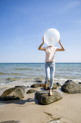 Girl standing on stones at the beach holding a balloon - OJF00287